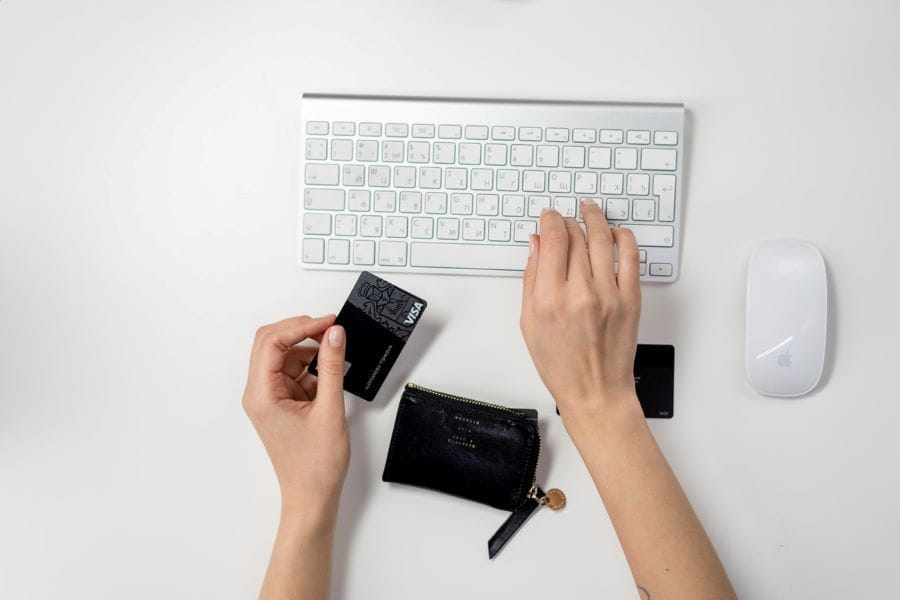 Someone typing on a computer keyboard, holding a credit card.