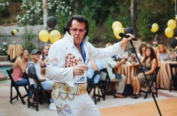 An Elvis impersonator performs at a backyard party.