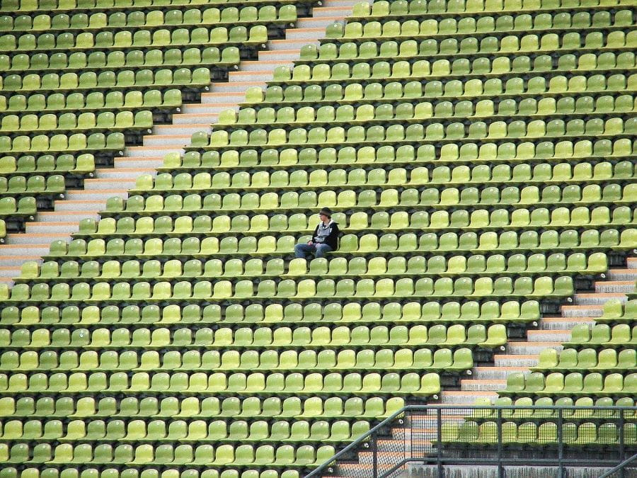 A single fan sitting in an empty football stadium.