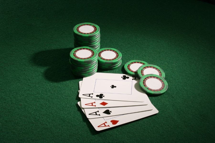 Four Aces cards lie on poker table beside chips.