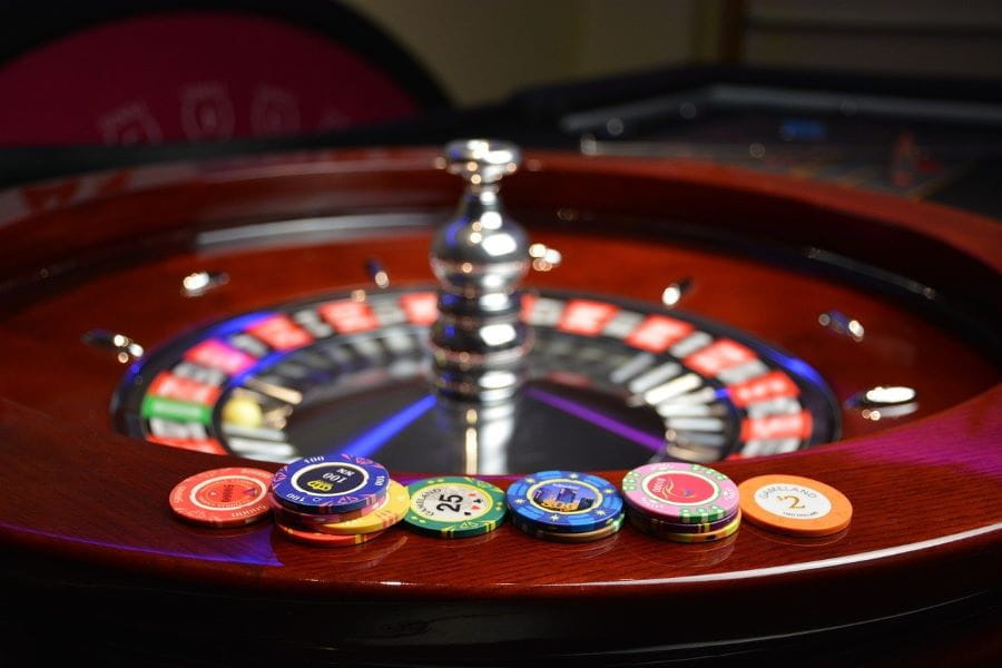 Gambling chips sit at the edge of roulette wheel.