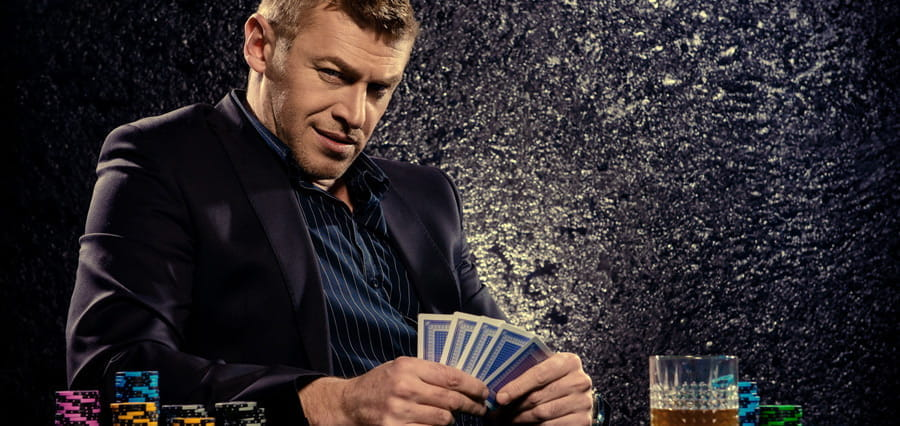 A man looking at the camera while holding a hand of cards.