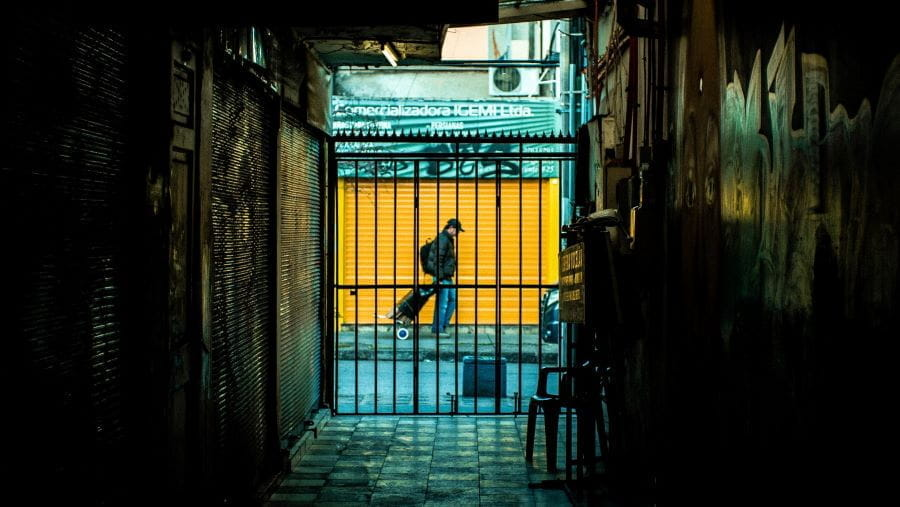 A gated alleyway looks out onto colorful closed storefronts in Santiago, Chile.
