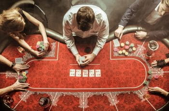 A poker table, with four players and a dealer.