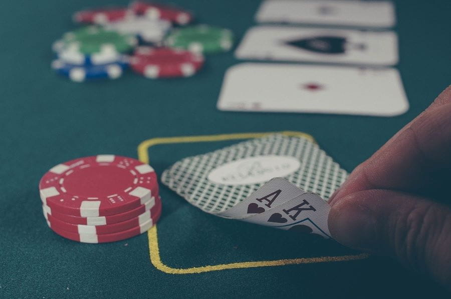 A person looking at their cards in a poker game.