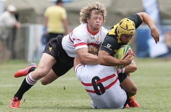 Two rugby players diving for the line in a tackle.