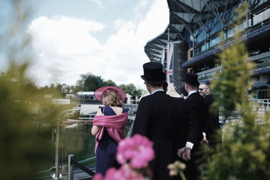 Men and women in formal clothes at the Royal Ascot horse race.