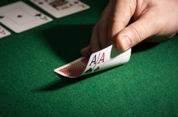 Two Ace cards lay face down with values revealed on poker table.