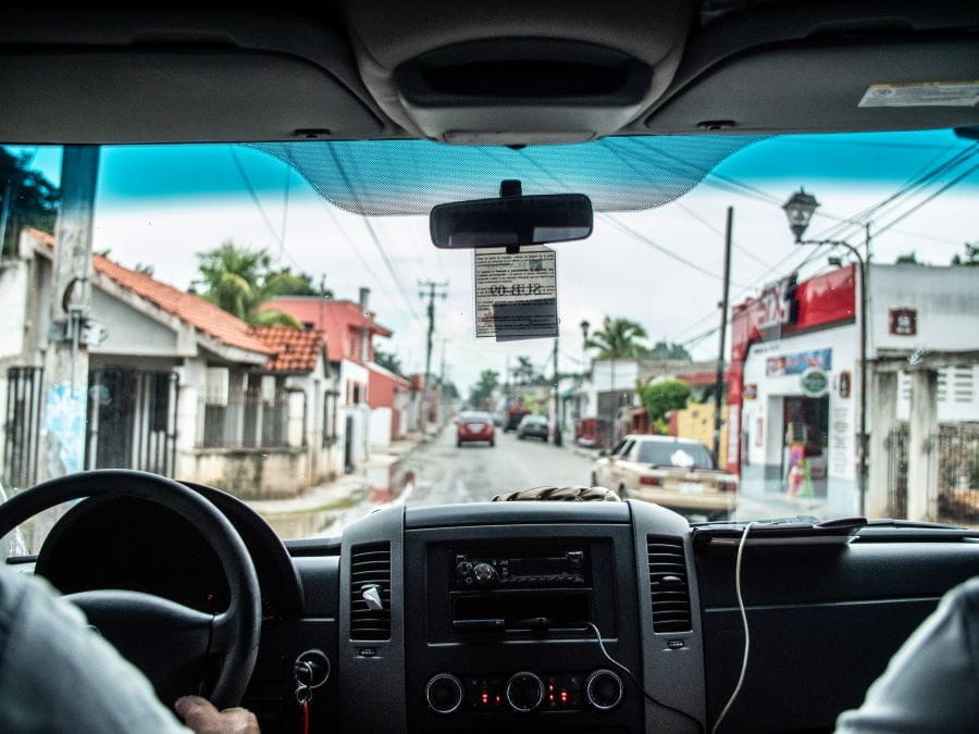 In the backseat of a car driving through a residential street in Mexico.