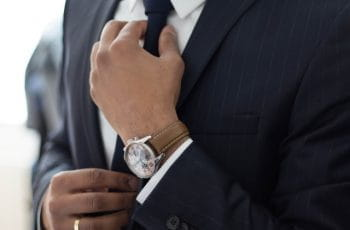A businessman in a suit and expensive watch adjusts his tie.