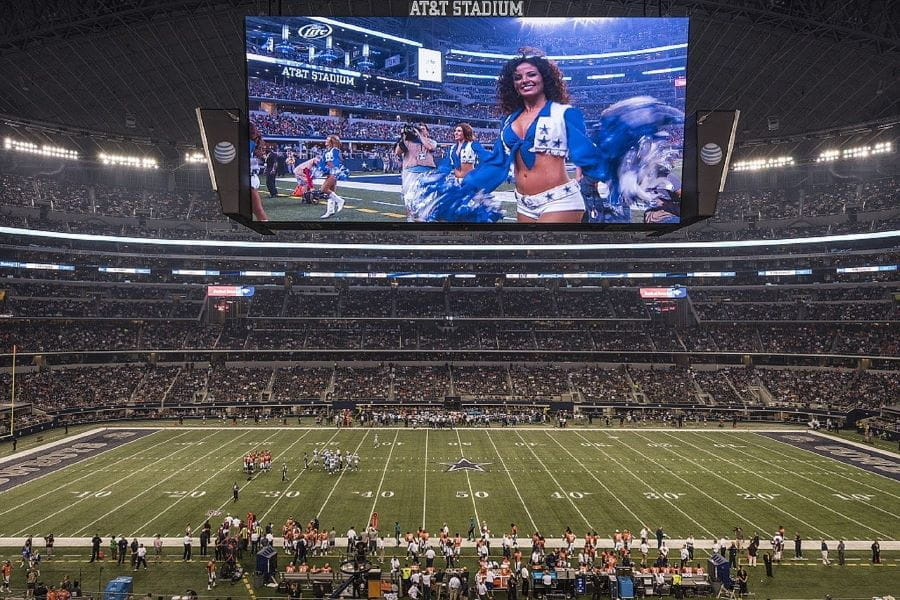 AT&T Stadium field before game with cheerleader on screen.