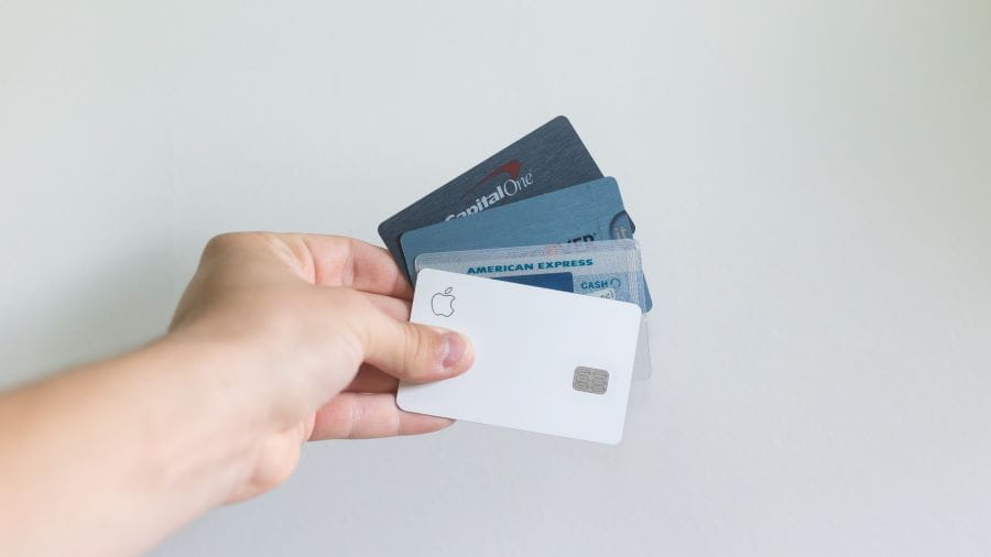 Hand holding out a selection of credit and debit cards.