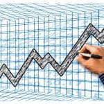 A business man drawing an upward graph representing profits.