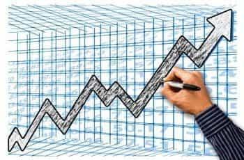 A business man drawing an upward graph representing profits.