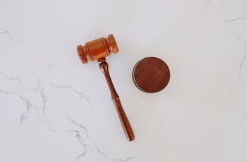 A wooden judge's gavel on white marble.