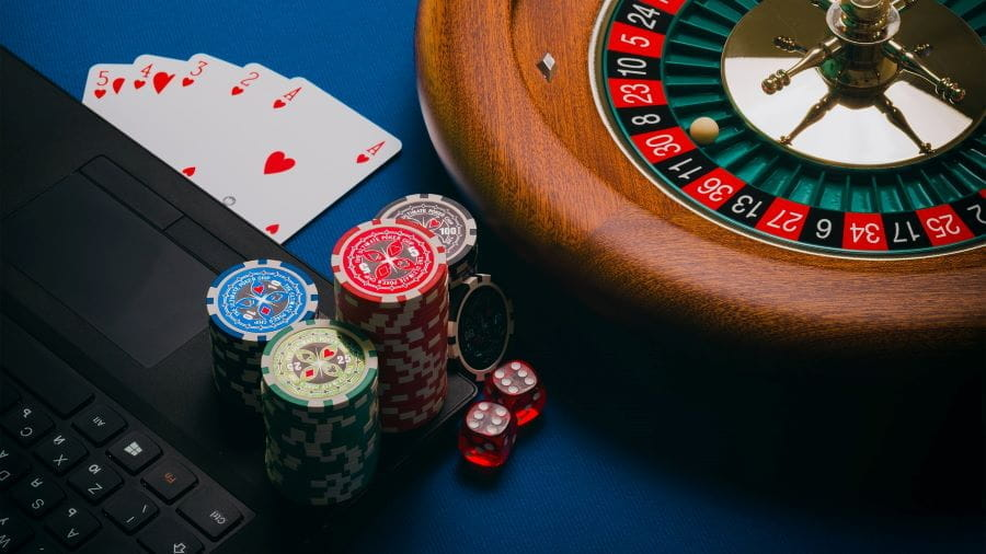 A roulette wheel, poker chips, playing cards and laptop, on blue felt.