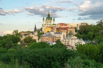 The city of Kyiv in Ukraine. There is a wooded area in the foreground.