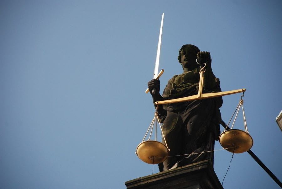 A statue of lady justice outside a courthouse. She is holding a sword and scales.
