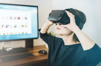 A woman sitting at a computer looks through a set of VR goggles.