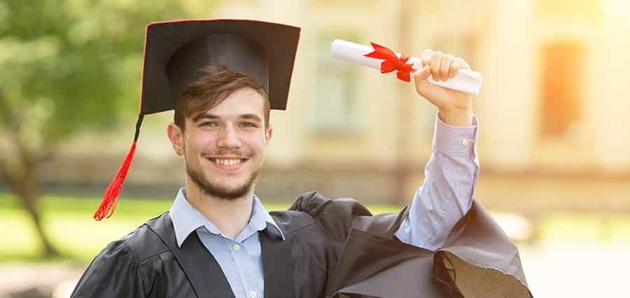 A graduate holding up a certificate.