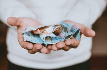 A person holds out hands with money.