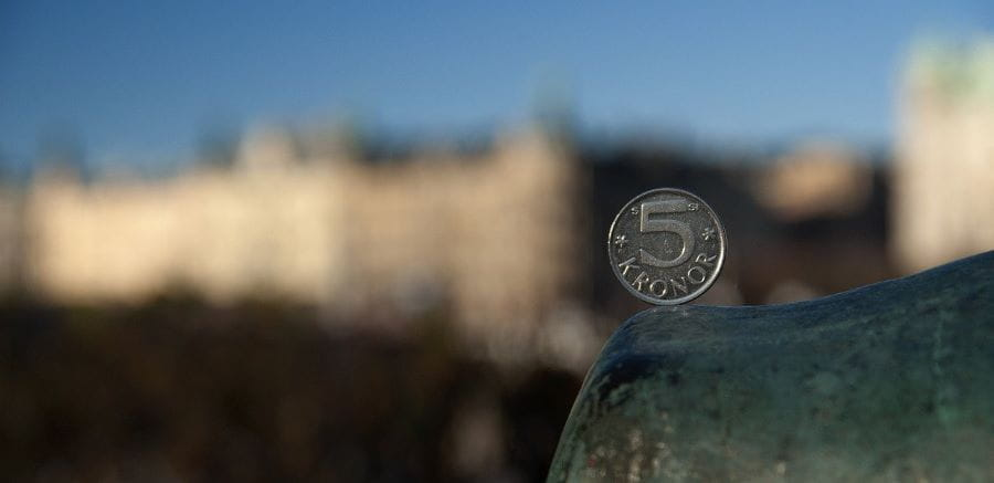 A Swedish coin balanced with a blurred Stockholm in the background.