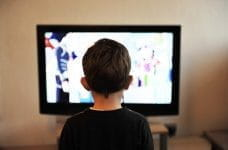 A small child watching television.