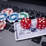 Dice, chips and a bankcard on top a laptop to symbolize online gambling.