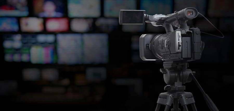 A TV camera with a blurred background of TV screens.