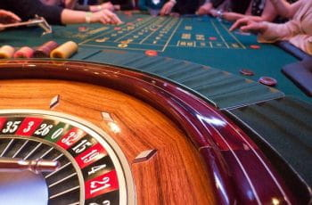 A roulette table in a casino with people around it.