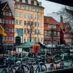 A row of bikes in front of houses in Copenhagen, Denmark.