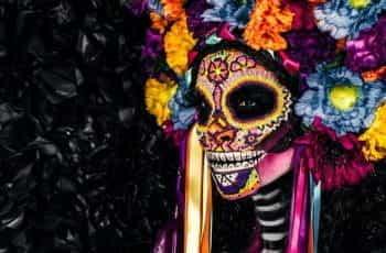 A woman wears an elaborate Día de Los Muertos costume.