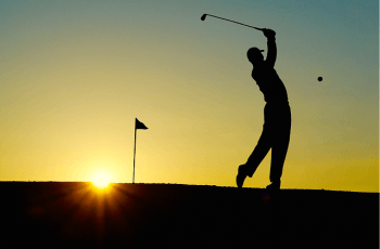 A golf player swings the club to hit a ball against the sunset.