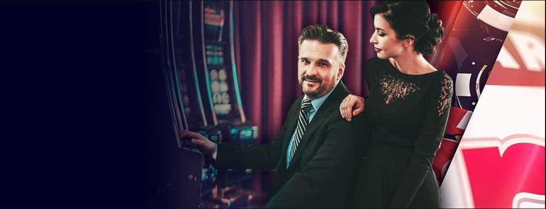 A man and woman sitting at a slot machine.