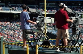 Two camera operators film a baseball game in an arena.