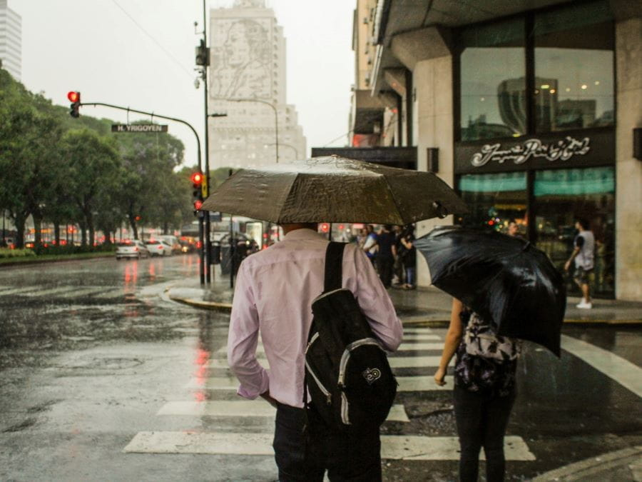 A couple holding an umbrella crosses the street on a rainy day in Buenos Aires, Argentina.