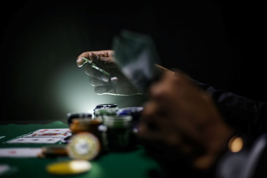 Gamblers play poker in a dark casino.