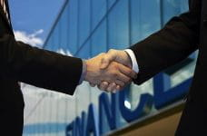 A deal is made with shaking hands in front of office.