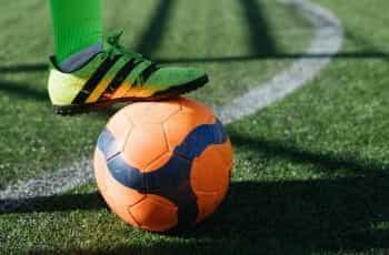A footballer with foot on an orange football.