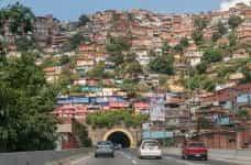 A roadway runs through a mountain of houses in Caracas, Venezuela.