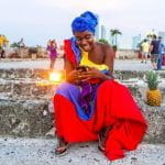 A woman in a brightly colored outfit in Cartagena, Colombia looks at her phone.