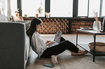 A white woman sits on the floor in her living room, looking at her laptop.