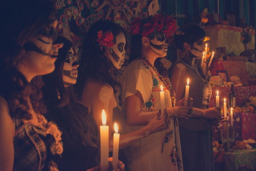 A line of women wearing face paint for Día de Los Muertos hold candles.