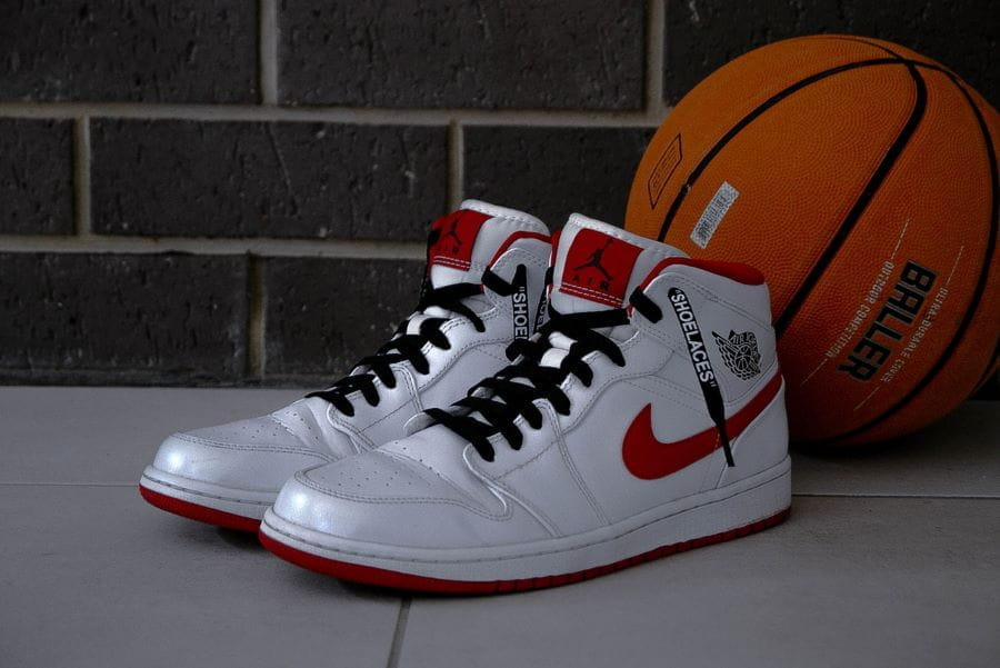 A white and red pair of Air Jordans lean against an orange basketball.