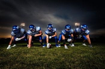 Five male American football players wearing blue uniforms prepare for their next play.