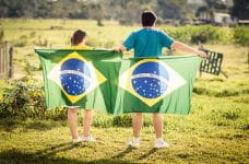 A man and a woman turn their backs to the camera and hold Brazilian flags behind them.
