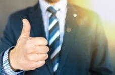 Businessman in suit with thumbs up.