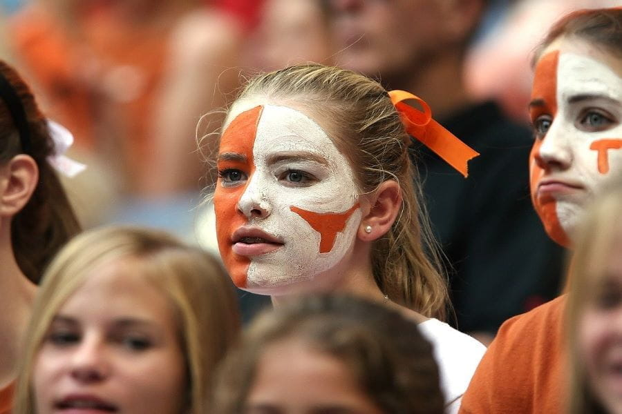A young sports fan with her face orange and white painted stands in the stands of a sports game.