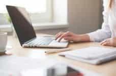 A woman uses a laptop on a desk.