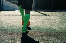 A footballer in green socks and boots, with foot on orange ball.